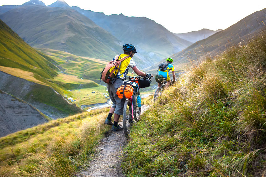 Biker pushes his bicycle up in high Caucasus mountains