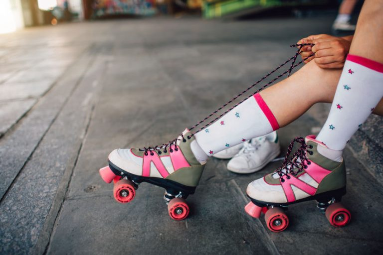 Girl is sitting on the floor and tying laces on her right roller. She is pulling them back. Also she put her right feet on the back roller's wheels.
