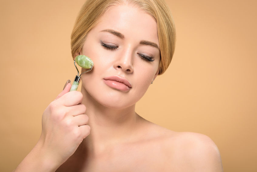 attractive young naked woman massaging face with jade roller and looking down isolated on beige